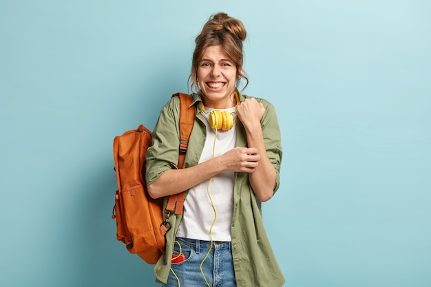 Mulher europeia insatisfeita esfrega as mãos, cerra os dentes, tem expressão facial insatisfeita, usa fones de ouvido, camisa e jeans