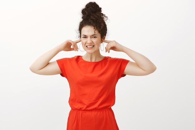 Mulher europeia irritada e descontente com cabelo encaracolado, usando um vestido fofo e cobrindo as orelhas com o dedo indicador