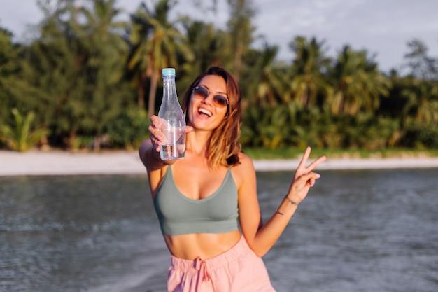 Mulher europeia jovem bonita feliz com uma garrafa de plástico de água na mão na praia