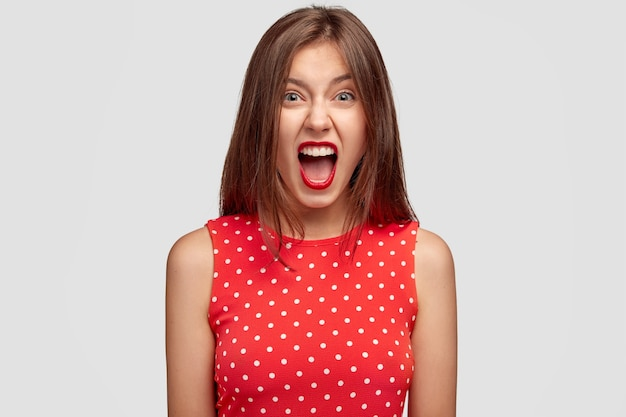 Mulher europeia jovem brava grita de aborrecimento, tem os lábios vermelhos, sendo irritada com alguém, vestida com um vestido elegante, isolada sobre uma parede branca. conceito de pessoas e emoções negativas
