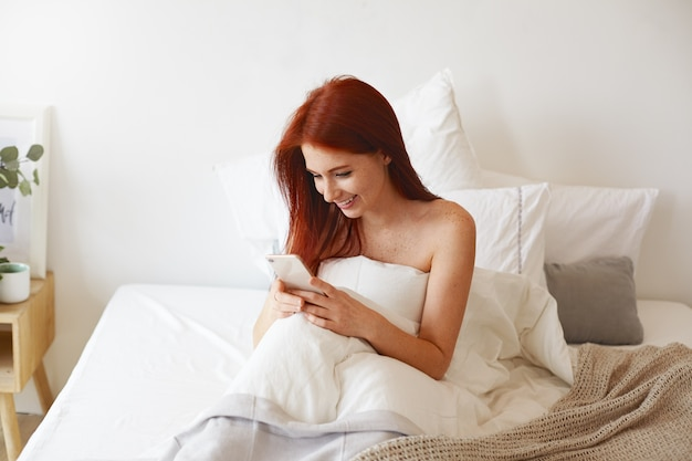 Mulher europeia jovem e atraente feliz com sardas e cabelos ruivos, sorrindo amplamente enquanto lê a mensagem de texto do namorado usando o telefone celular na cama, sem roupa, cobrindo o corpo com um cobertor