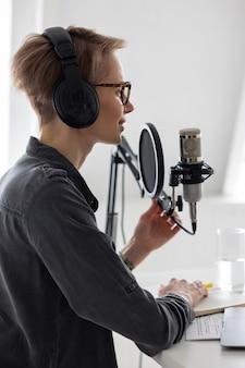 Mulher européia jovem e confiante gravando um podcast em um estúdio de gravação