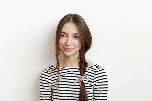 Mulher europeia jovem feliz com um penteado bagunçado, vestida com uma blusa listrada e um olhar alegre