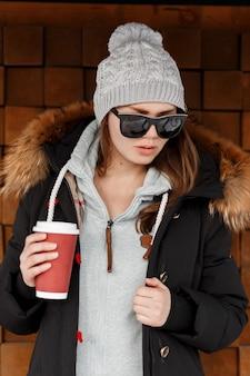 Mulher europeia jovem hippie com um chapéu de malha com um moletom cinza com uma jaqueta de inverno em óculos de sol pretos se passando perto de uma parede de madeira vintage e segurando uma xícara de café vermelha. garota fashion