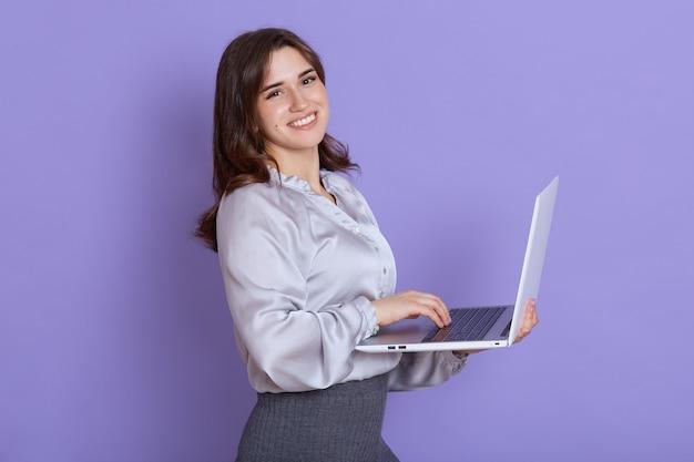 Mulher europeia jovem sorridente, vestindo roupas elegantes posando isolado na parede lilás, segurando e trabalhando no computador laptop pc, com expressão feliz.