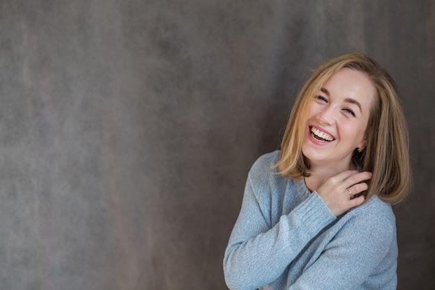 Mulher europeia loira bonita feliz tocando seus cabelos