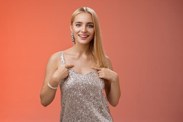 Mulher europeia loira confiante arrogante e bonita em um vestido prateado luxuoso apontando a si mesma sorrindo orgulhosamente e se gabando de falar seus próprios objetivos de realizações em pé fundo vermelho autoconfiante.