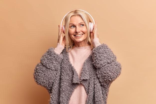 Mulher europeia loira elegante com sorriso agradável usa fones de ouvido estéreo curtindo a música favorita com expressão sonhadora usa casaco de pele isolado sobre parede marrom