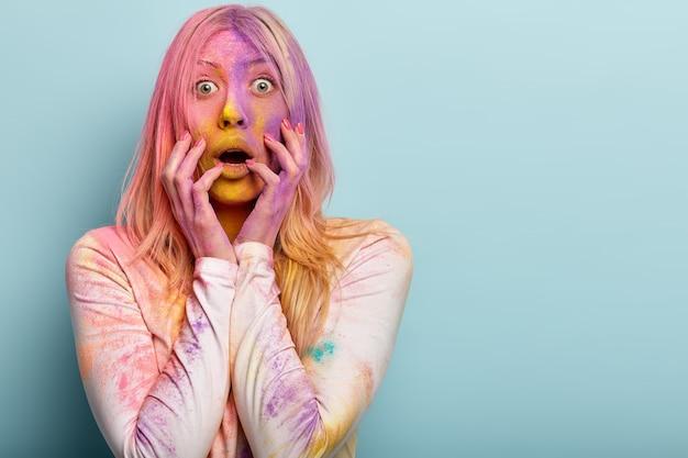 Mulher européia loira em choque intenso lambuzada de pó multicolorido, engasga e abre a boca