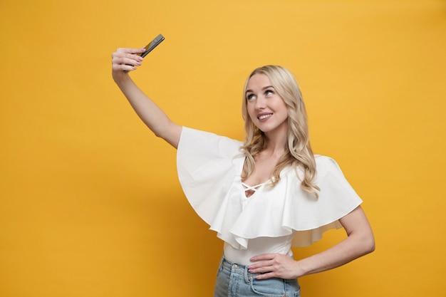 Mulher europeia loira feliz na blusa branca, fazendo selfie com smartphone. copie o espaço