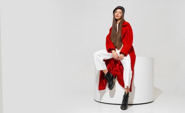Mulher europeia morena elegante com casaco vermelho e chapéu preto, posando na parede branca.