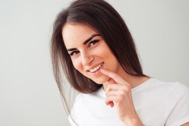 Mulher europeia mostra com o dedo indicador para o dente, satisfeito depois de visitar o dentista. clareamento dos dentes.