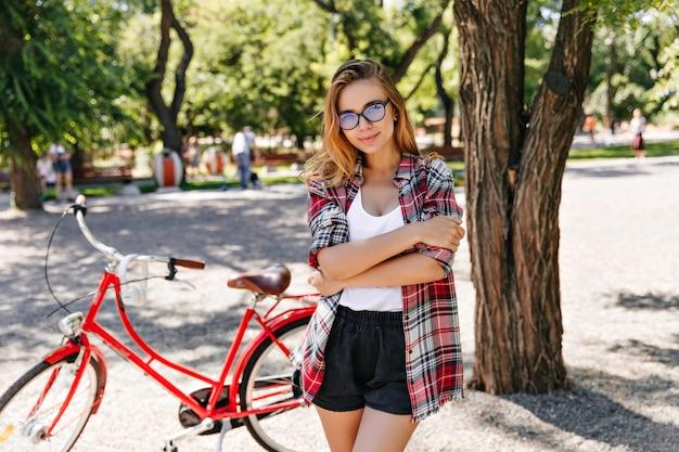 Mulher europeia na moda posando com bicicleta na rua. debonair modelo feminino em pé no parque com bicicleta vermelha.