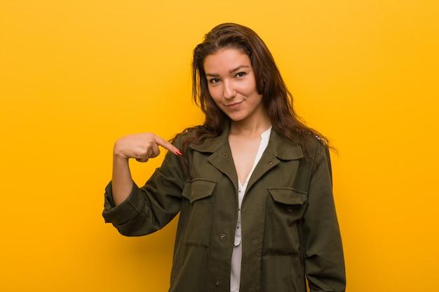 Mulher européia nova isolada sobre a pessoa amarela que aponta à mão a uma cópia da camisa, orgulhosa e confiante