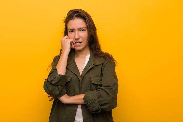 Mulher européia nova isolada sobre as unhas cortantes do fundo amarelo, nervosas e muito ansiosas.