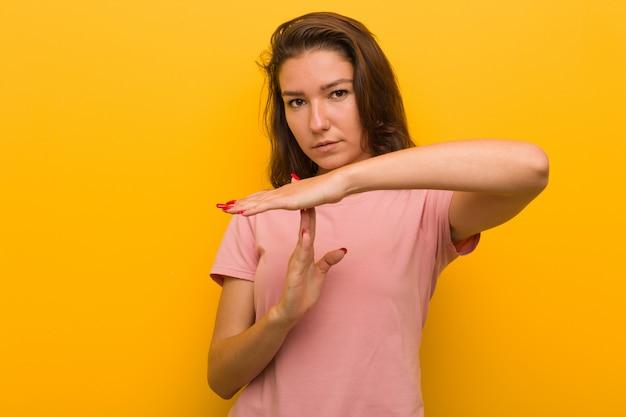 Mulher européia nova isolada sobre o fundo amarelo que mostra um gesto do intervalo.