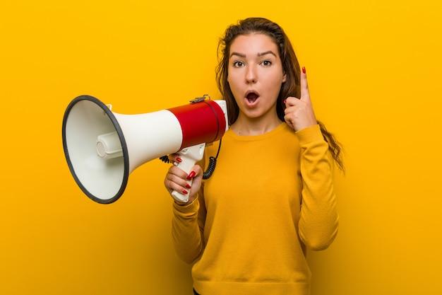 Mulher européia nova que guarda um megafone que tem alguma grande ideia, conceito da faculdade criadora.