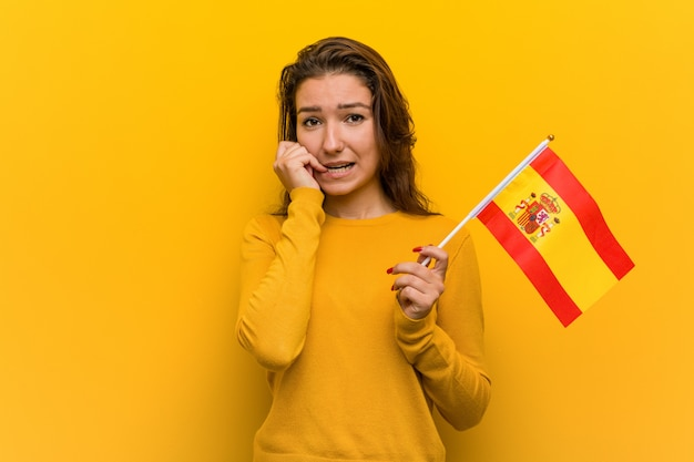 Mulher européia nova que prende as unhas cortantes de uma bandeira espanhola, nervosas e muito ansiosas.