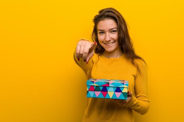 Mulher européia nova que prende os sorrisos alegres de um presente que apontam para frontear.