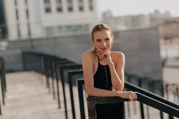 Mulher europeia posando para a câmera com um sorriso enquanto treina lá fora em um dia ensolarado
