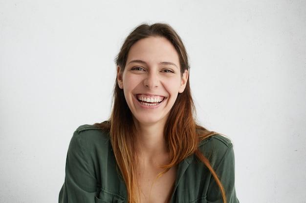 Mulher européia positiva com cabelo comprido feliz, sorrindo agradavelmente