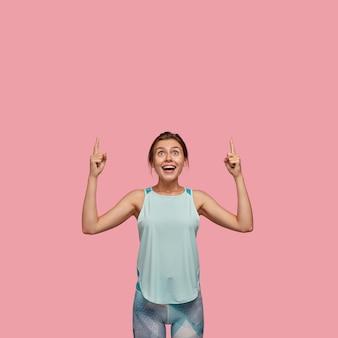 Mulher européia positiva com expressão alegre, aponta com os dois dedos indicadores para cima, vestida com colete casual e leggings, modelos sobre parede rosa. conceito de propaganda. olhe para o teto!