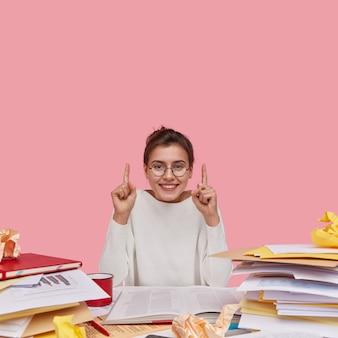 Mulher europeia positiva com expressão facial alegre, vestida com roupas casuais brancas, mostra a direção de cabeça, usa documentos em papel, tem um sorriso cheio de dentes