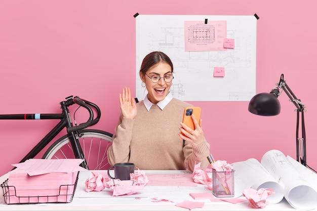 Mulher europeia positiva faz videochamada acenando na palma da mão, segura smartphone moderno funciona em relatório prepara poses de tarefa em casa no desktop