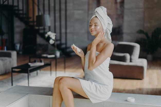 Mulher europeia relaxada tem beleza natural demonstra pernas delgadas aplica loção facial nutritiva, cuida da pele, gosta de tratamentos de higiene em casa, posa contra o interior aconchegante do quarto