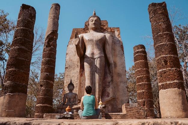 Mulher européia religiosa do turista que sightseeing os templos históricos em sukhothai. buddha ereto wat saphan hin em tailândia.