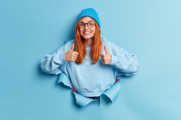Mulher europeia ruiva alegre faz gesto com o polegar para cima e excelente sinal que aprova algo sorri amplamente usa chapéu e o suéter quebra pelo buraco do papel