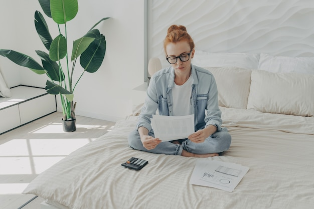 Mulher europeia ruiva bonita calcula despesas e administra orçamento doméstico