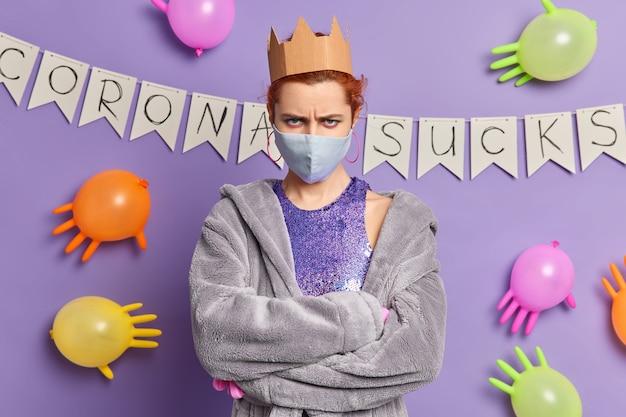 Mulher europeia ruiva zangada parece irritada mantém os braços cruzados e usa máscara descartável para se proteger do coronavírus vestida com manto doméstico posa contra uma parede roxa com balões coloridos