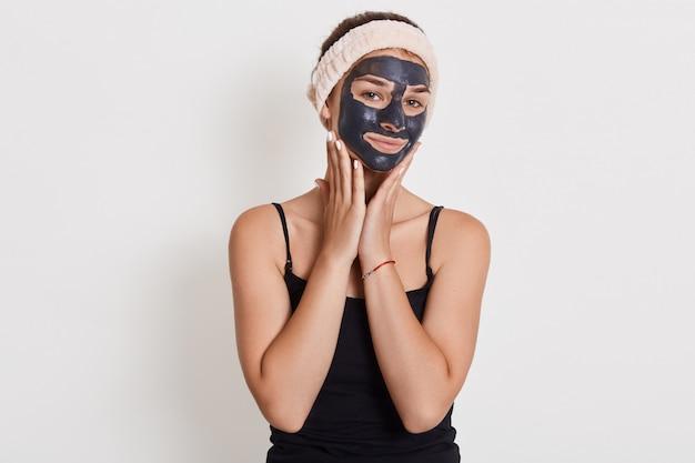Mulher europeia satisfeita aplica máscara de argila nutritiva no rosto, tem expressão alegre, toca as bochechas, tendo problema de pele seca.