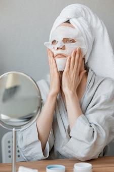 Mulher europeia sentada em frente ao espelho e aplicando uma máscara hidratante de pano branco nela