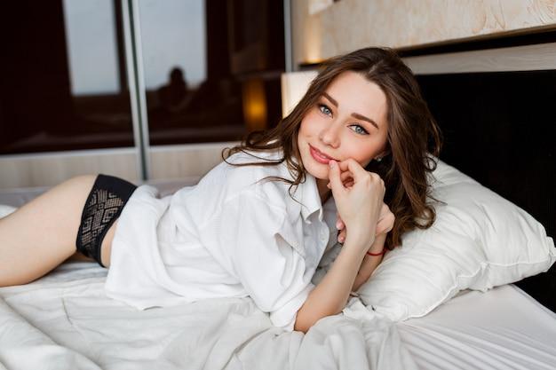 Mulher europeia sexy com cabelos ondulados, deitada de bruços na cama branca.