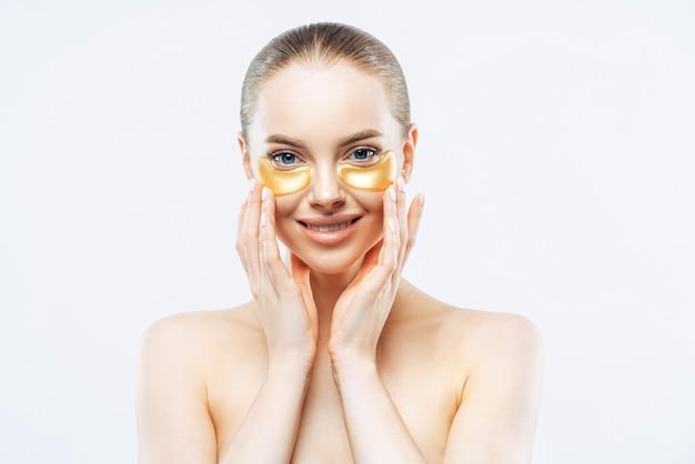 Mulher europeia sorridente e carinhosa tocando o rosto, aplicando o tapa-olho