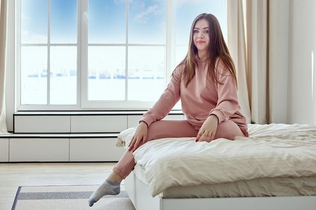 Mulher europeia sorridente se senta na cama em frente a uma grande janela, vestida com um terno rosa.