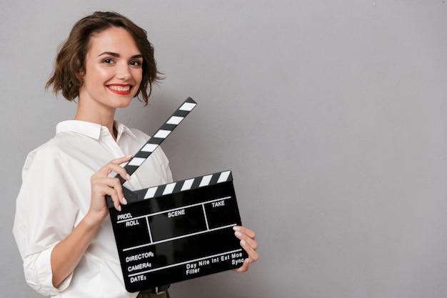 Mulher europeia sorrindo e segurando claquete preta, isolada sobre uma parede cinza