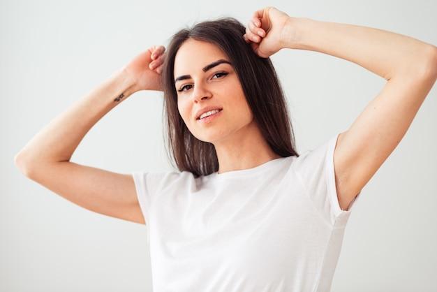 Mulher européia sorrindo, mantendo as mãos atrás da cabeça. garota legal em uma camiseta branca limpa, sobre um fundo claro.