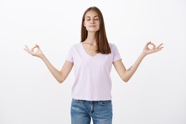 Mulher europeia tranquila e encantadora praticando ioga em pé em pose de lótus com os dedos em gesto zen e olhos fechados sendo determinada durante a meditação