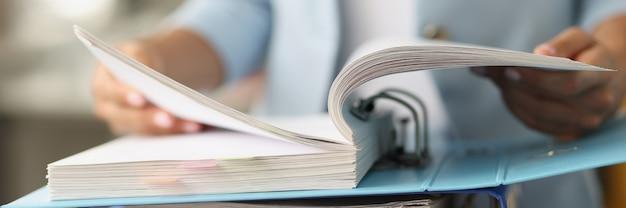 Mulher examinando informações em uma pasta com documentos em close-up