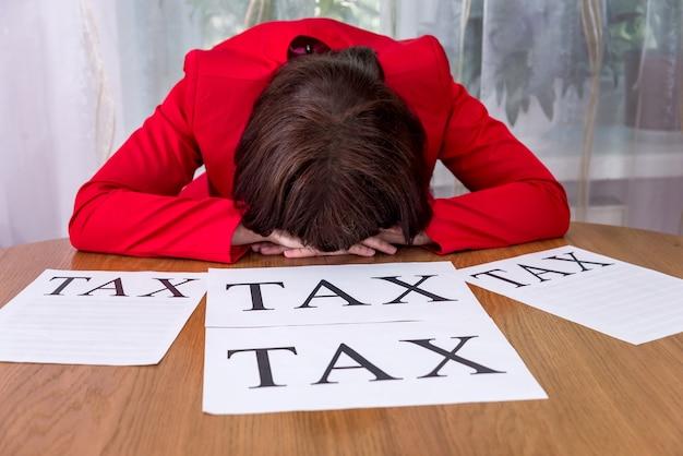 Mulher exausta com os impostos deitada de cabeça na mesa