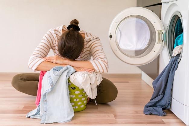 Mulher exausta de lavar roupa