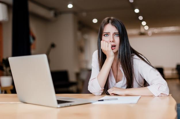 Mulher exausta e cansada no escritório com laptop