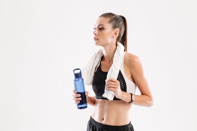 Mulher exausta fitness suada com uma toalha no pescoço