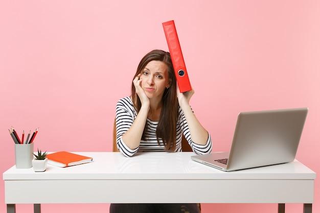 Mulher exausta, segurando uma pasta vermelha com um documento em papel perto da cabeça trabalhando no projeto enquanto está sentado no escritório com o laptop isolado no fundo rosa pastel. conceito de carreira empresarial de realização. copie o espaço.
