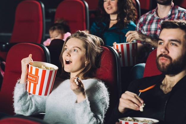 Mulher excitada assistindo filme no cinema Foto gratuita