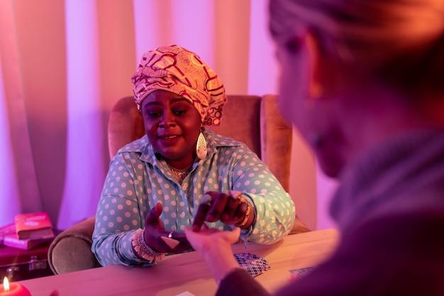 Mulher excitada. cartomante rechonchudo afro-americano usando um anel enorme e parecendo animado