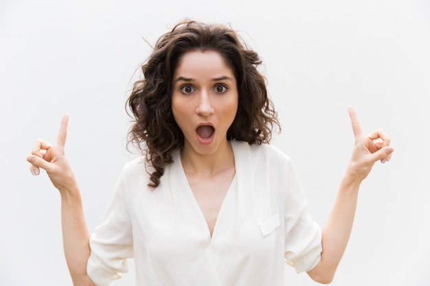 Mulher excitada chocada com a boca aberta, apontando os dedos para cima